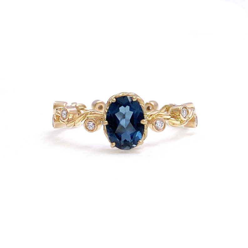 London-blue-topaz Solitaire with JeweLyrie Signature twist wave shank with diamondsin 14k and 18k made to order by JeweLyrie
